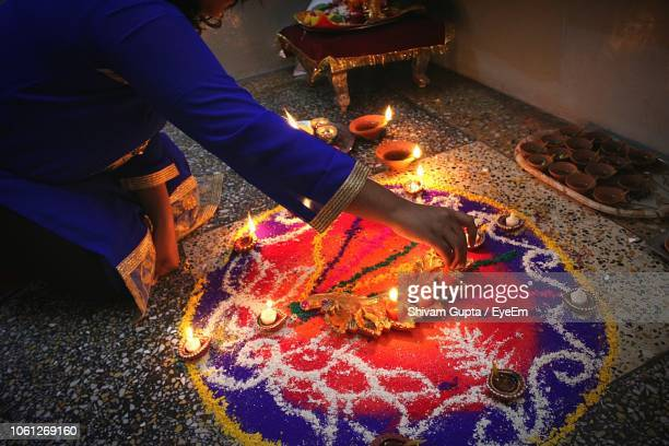 midsection of woman decorating rangoli with candles on floor - rangoli stock pictures, royalty-free photos & images