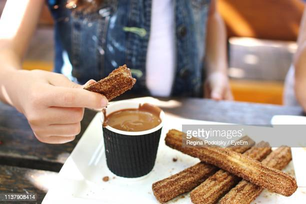 midsection of woman dipping churro in chocolate at table - churro stock photos and pictures