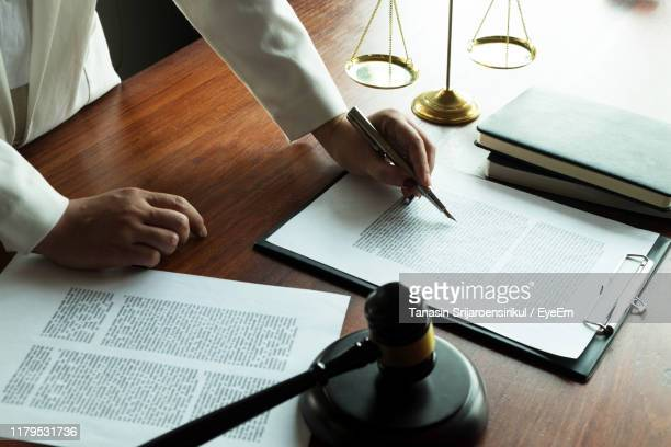 midsection of woman doing paper work on table - legislation stock pictures, royalty-free photos & images