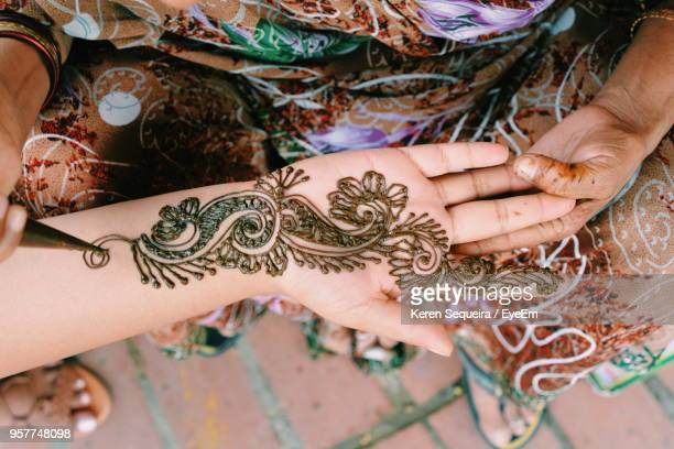 Midsection Of Woman Drawing Henna Tattoo On Hand