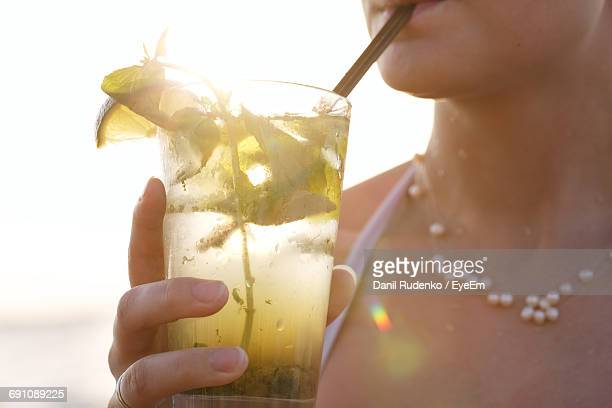 midsection of woman drinking mojito - mojito stock photos and pictures