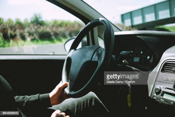 Midsection Of Woman Driving Car On Sunny Day