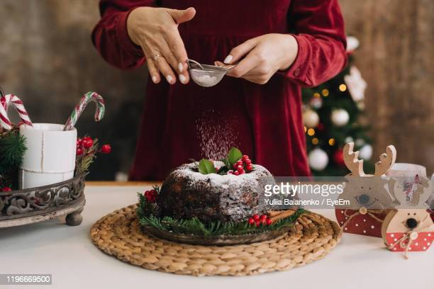 midsection of woman dusting powder sugar on cake - dessert stock pictures, royalty-free photos & images