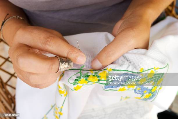 Midsection Of Woman Embroidering On Fabric