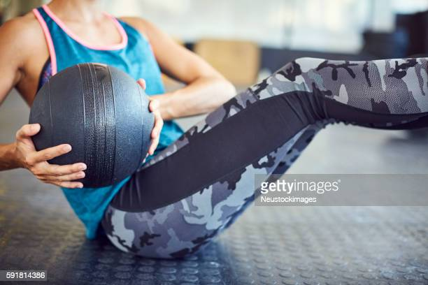 midsection of woman exercising with medicine ball in gym - medicine ball stock pictures, royalty-free photos & images