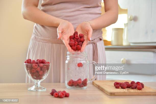 Midsection Of Woman Filing Jar With Raspberries At Table