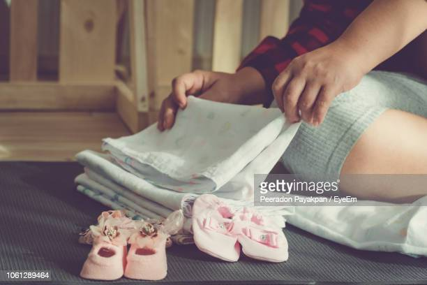 midsection of woman folding textiles by baby booties on bed at home - baby clothing stock pictures, royalty-free photos & images
