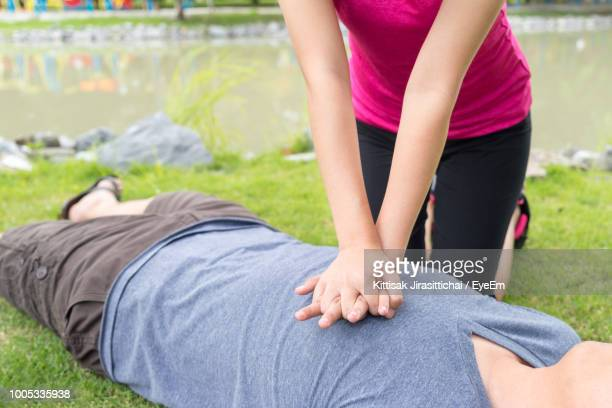 midsection of woman giving cpr to man by lake on field - cpr stock photos and pictures
