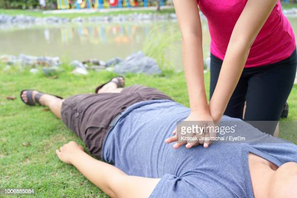 midsection of woman giving cpr to unconscious victim lying on field - gestes photos et images de collection