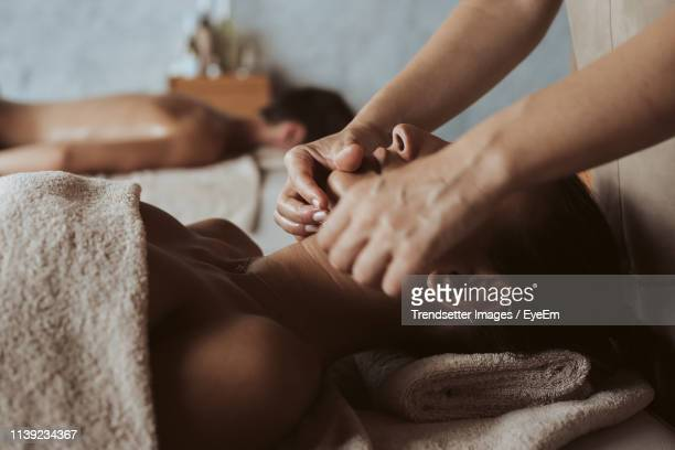 midsection of woman giving head massage to customer at spa - マッサージ ストックフォトと画像