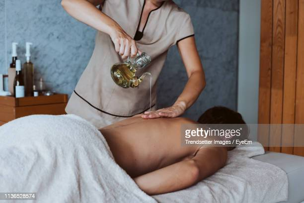 midsection of woman giving massage to young man in spa - massage homme femme photos et images de collection