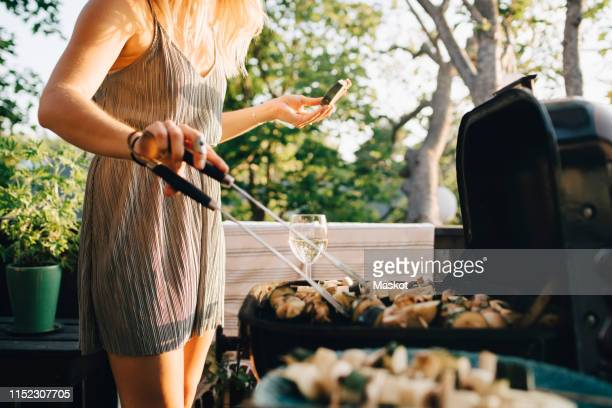 midsection of woman grilling vegetables on barbecue while eating watermelon - barbecue stock pictures, royalty-free photos & images