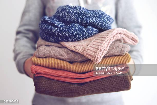 midsection of woman hand holding sweaters - abiti pesanti foto e immagini stock