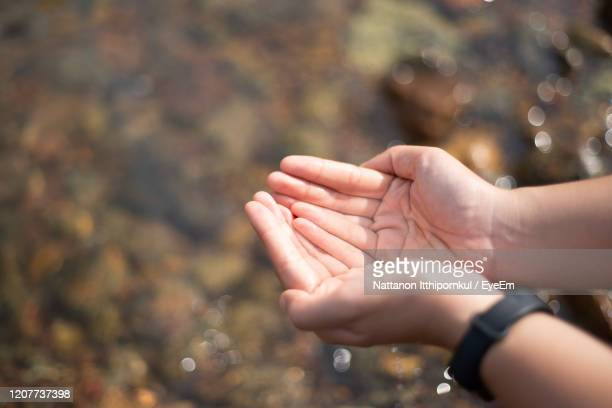 midsection of woman hands on water - 救う ストックフォトと画像