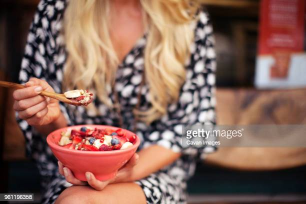 Midsection of woman having breakfast cereal while sitting at home