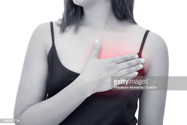 midsection of woman having chest pain against white background - heart attack stock photos and pictures