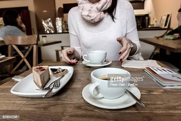 Midsection Of Woman Having Coffee And Pastry At Cafe