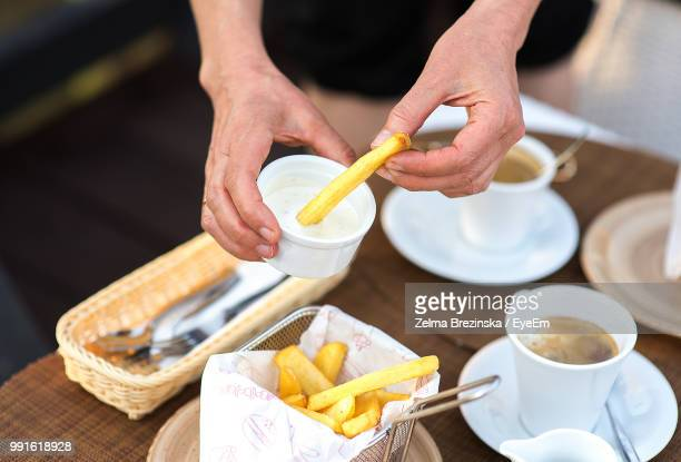 Midsection Of Woman Having French Fries At Table