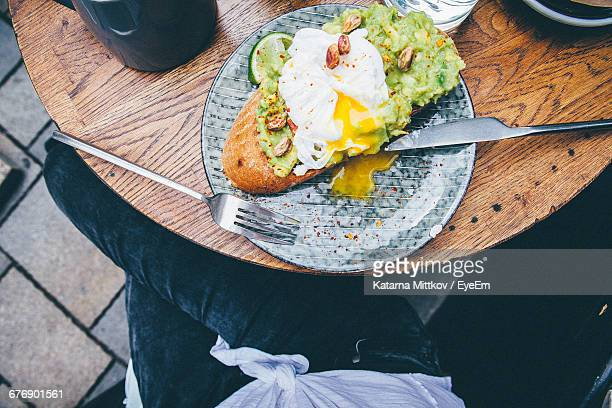Midsection Of Woman Having Open Faced Sandwich At Sidewalk Cafe