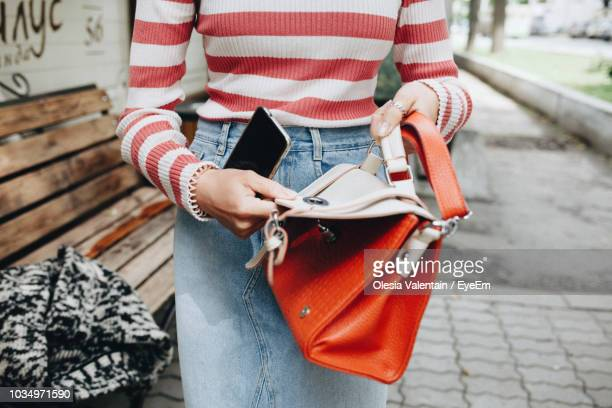 midsection of woman holding bag - borsetta da sera foto e immagini stock