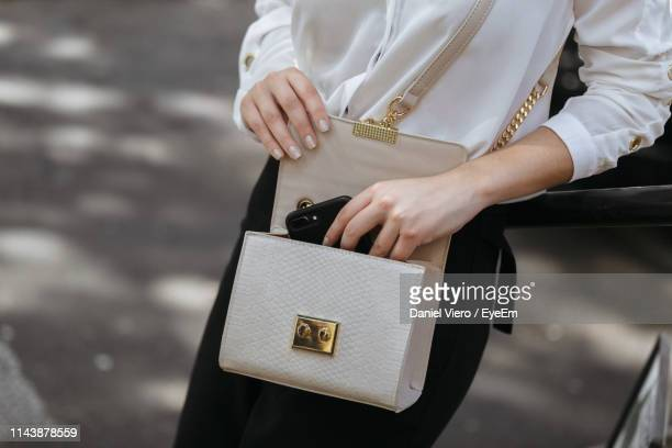 midsection of woman holding bag while standing outdoors - バッグ ストックフォトと画像