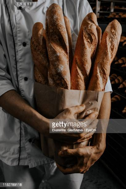 midsection of woman holding baguette in home - baguette stock pictures, royalty-free photos & images