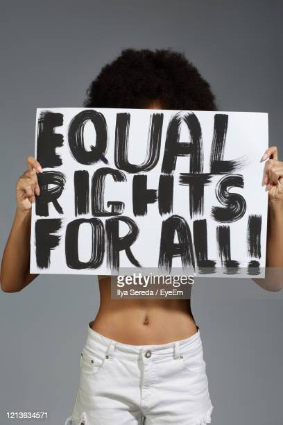 midsection of woman holding banner while standing against gray background - placard stock pictures, royalty-free photos & images