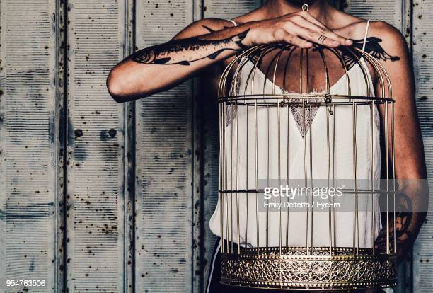 midsection of woman holding birdcage - confined space stock pictures, royalty-free photos & images