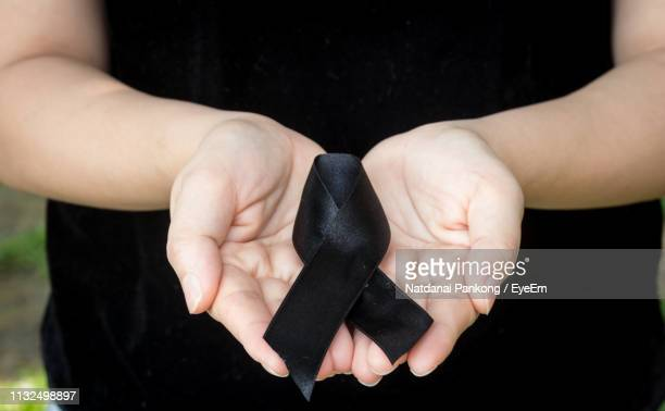 midsection of woman holding black ribbon - mourning stock pictures, royalty-free photos & images