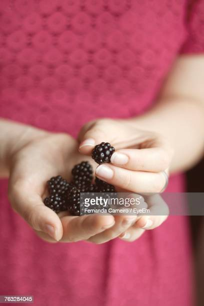 Midsection Of Woman Holding Blackberries