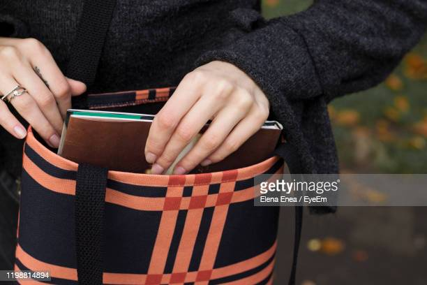 midsection of woman holding book - shoulder bag stock pictures, royalty-free photos & images