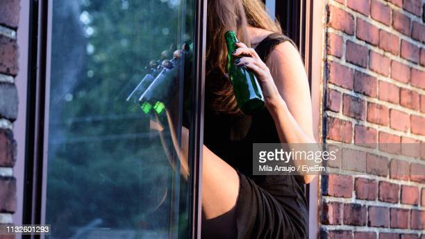Midsection Of Woman Holding Bottle While Sitting By Window
