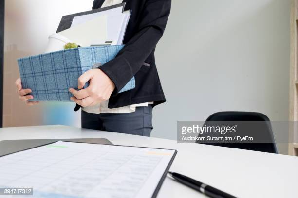 midsection of woman holding box by table at office - quitting a job stock pictures, royalty-free photos & images