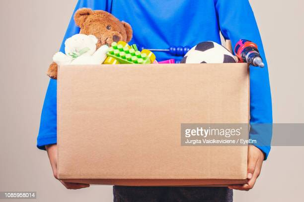 midsection of woman holding box full of toys for donation - toy box stock pictures, royalty-free photos & images