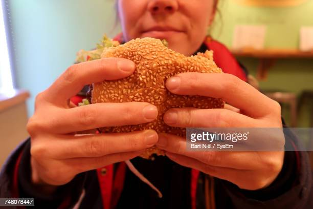 Midsection Of Woman Holding Burger At Restaurant