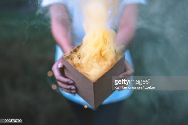 Midsection Of Woman Holding Burning Box