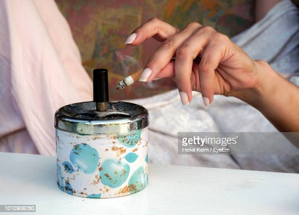 midsection of woman holding burnt cigarette - ash stock photos and pictures