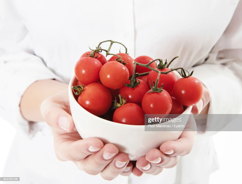 Midsection Of Woman Holding Cherry Tomatoes In Bowl : Stock Photo