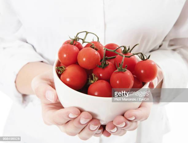 Midsection Of Woman Holding Cherry Tomatoes In Bowl