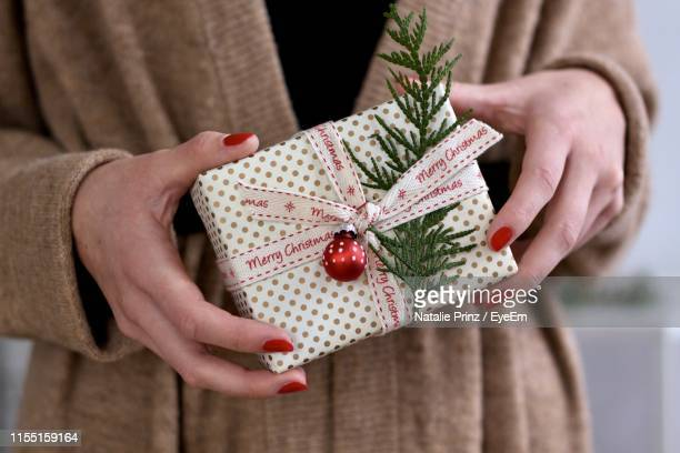 midsection of woman holding christmas present - red nail polish stock pictures, royalty-free photos & images