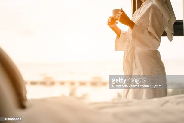midsection of woman holding coffee cup by window in hotel room - bathrobe stock pictures, royalty-free photos & images