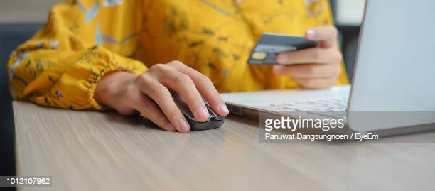 midsection of woman holding credit card while using laptop at table - computer mouse stock pictures, royalty-free photos & images
