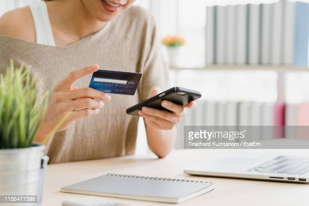 midsection of woman holding credit card while using mobile phone for online shopping on table - home shopping stock pictures, royalty-free photos & images