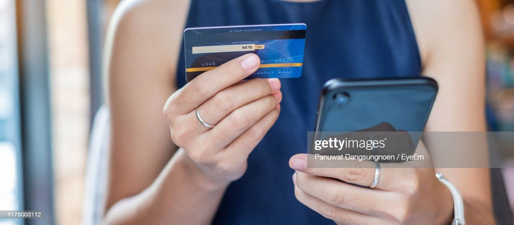 Midsection Of Woman Holding Credit Card While Using Mobile Phone For Online Shopping : Stock Photo