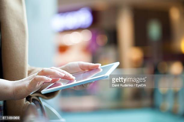 Midsection Of Woman Holding Digital Tablet