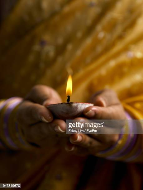 midsection of woman holding diya - diwali stock photos and pictures