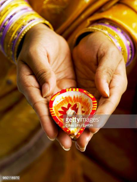 midsection of woman holding diya - diya oil lamp stock pictures, royalty-free photos & images