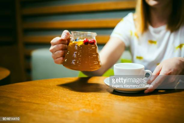 midsection of woman holding drink and coffee cup on table - coffee drink stock pictures, royalty-free photos & images