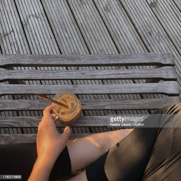 midsection of woman holding drink in jar while sitting on floor - sandhurst stock pictures, royalty-free photos & images
