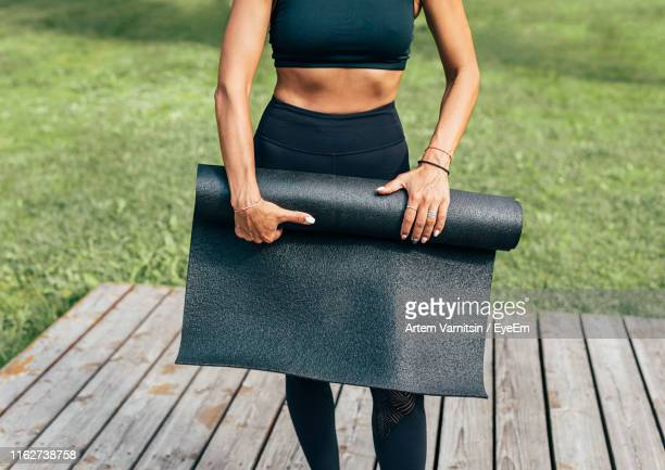 midsection of woman holding exercise mat while standing outdoors - エクササイズマット ストックフォトと画像